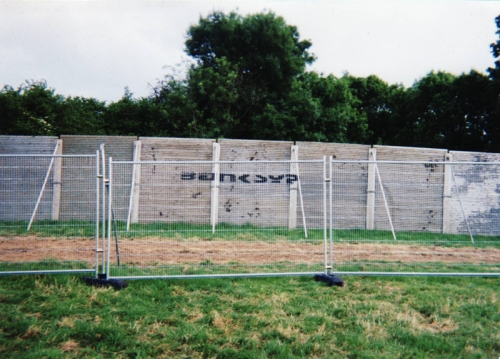 banksy-fence-at-top-of-stone-circle-glasto-2000
